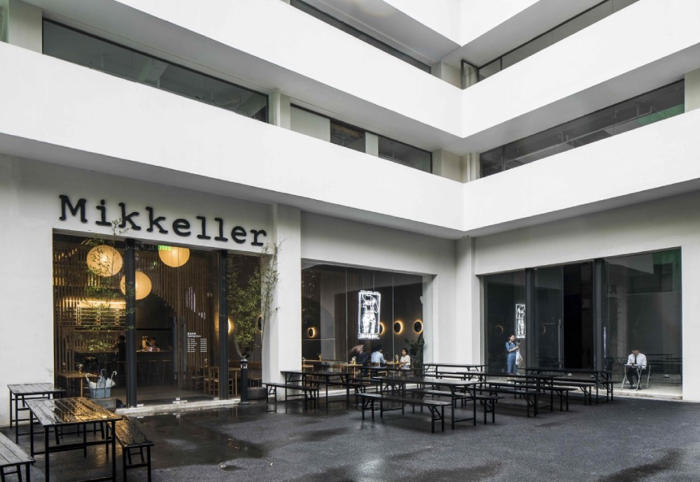 The new Mikkeller Shanghai bar in a tall white building by an open yard