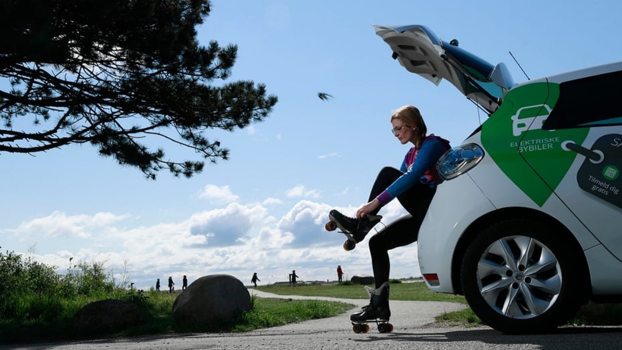 Woman putting on roller skates on the back of an electric car