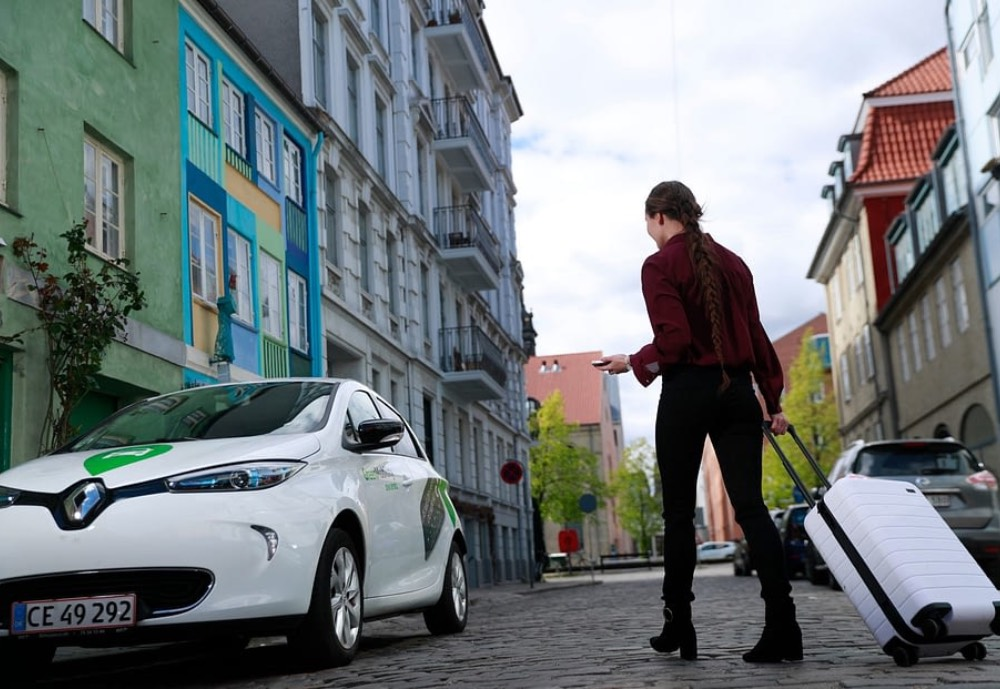 Woman with suitcase walking over to an electric car