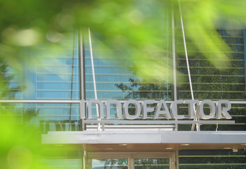 Innofactor sign on a building entrance seen through leaves
