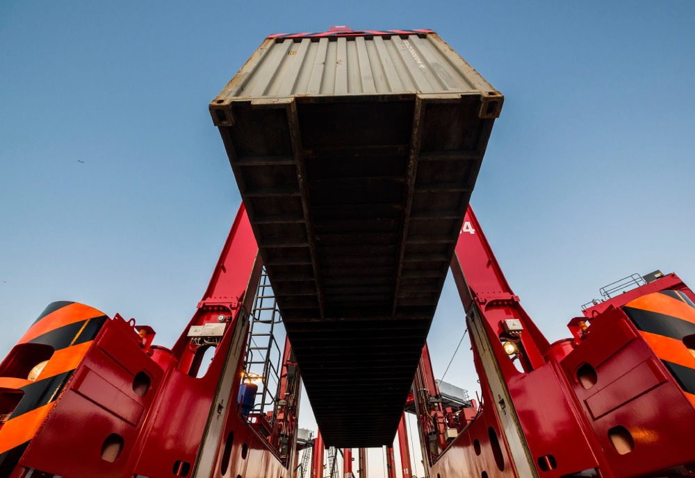 A red straddle carrier lifting a container