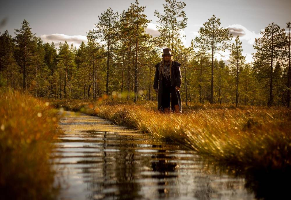 Korpiklaani band member standing in a Finnish swamp