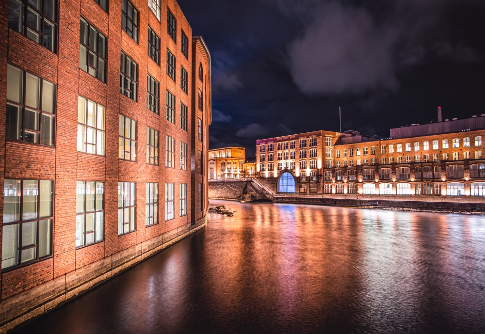Brick buildings by a river at night
