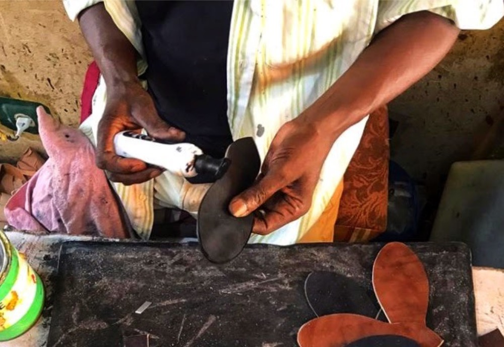 Man puts substance from a tube on the sole of a shoe