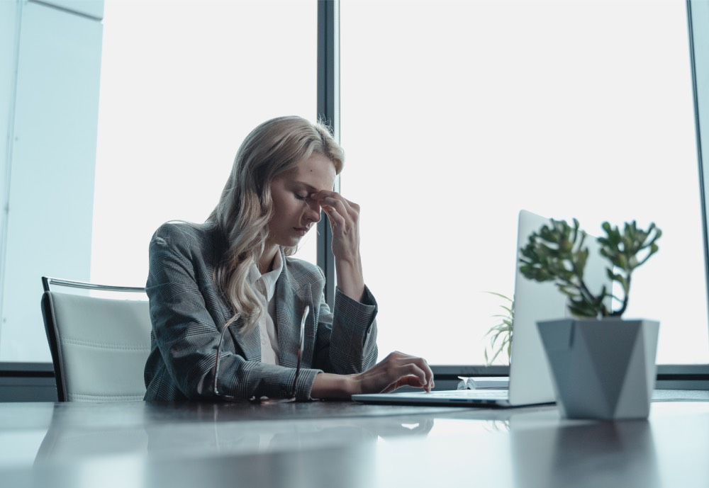 An office worker clinching her nose in exasperation