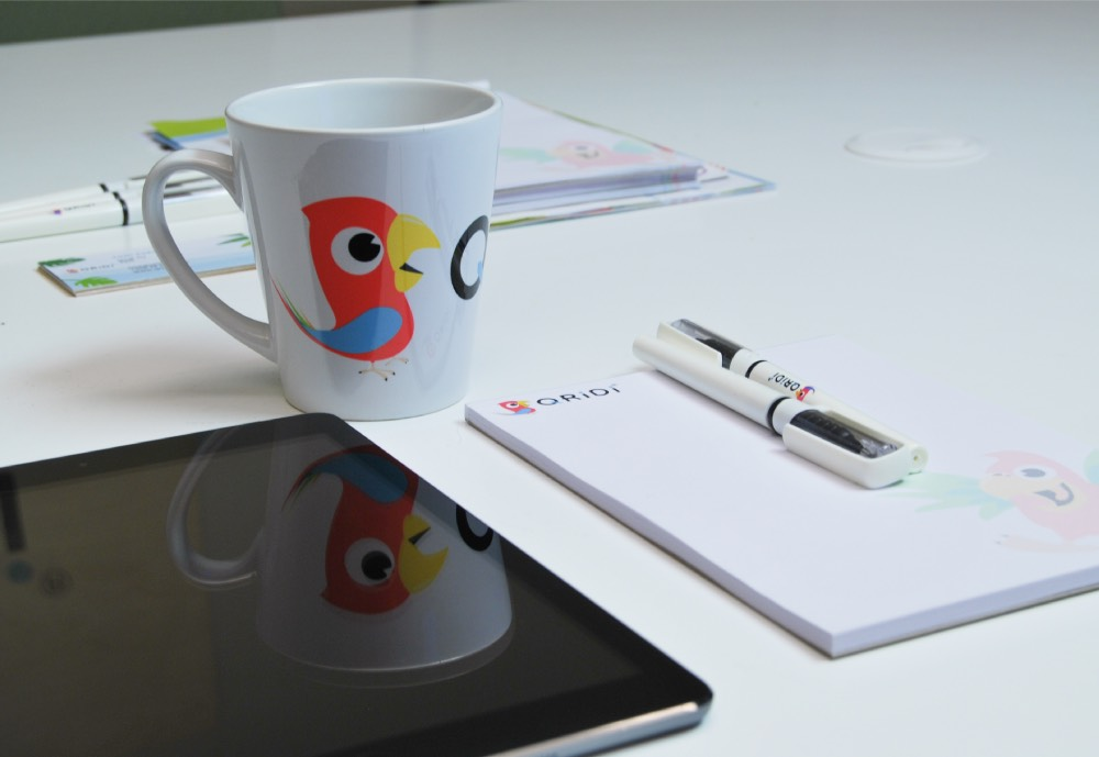 A tablet, a cup with Qridi's parrot logo and a some paper and a pen