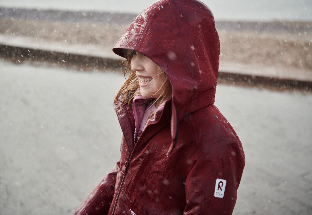 A young girl wearing a red jacket outside in rainy weather