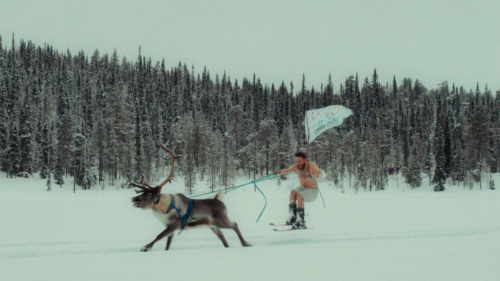 half-naked man reindeer-skiing with a flag
