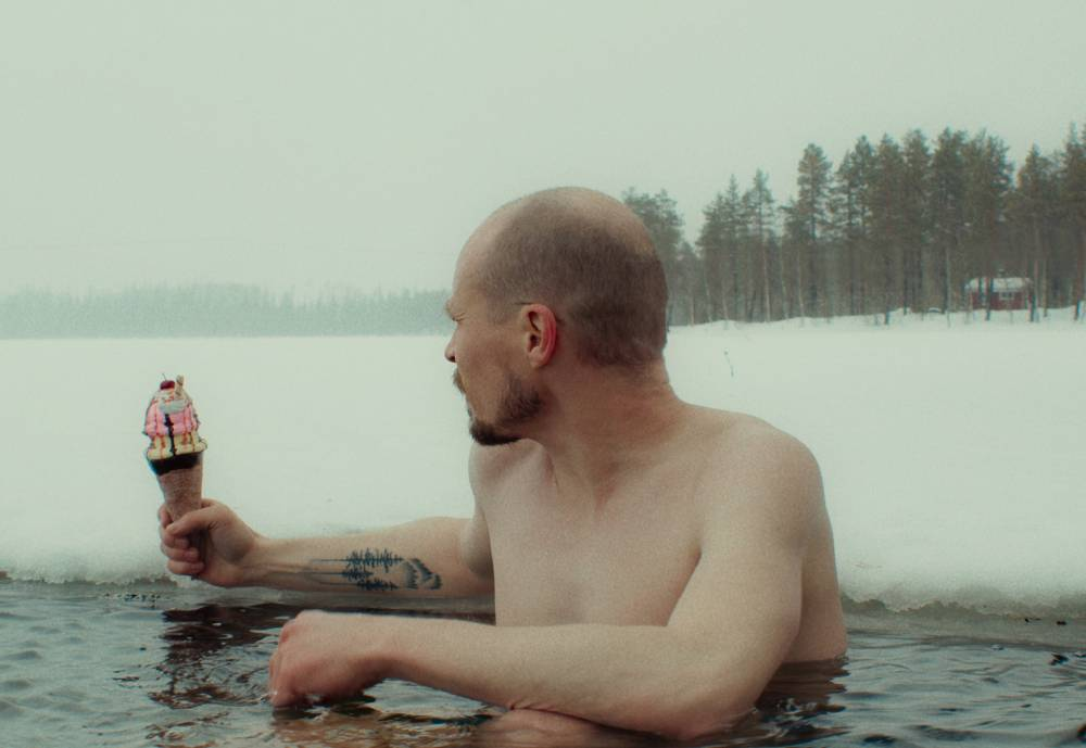 man eating an ice cream in a frozen lake