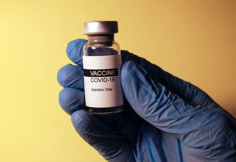 A gloved hand holding a small bottle with a COVID-19 Vaccine label