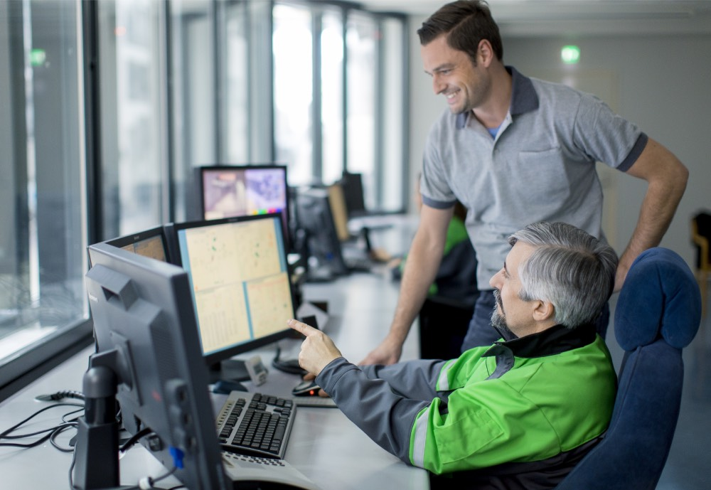 An elderly man in an overall and a younger man look at monitors