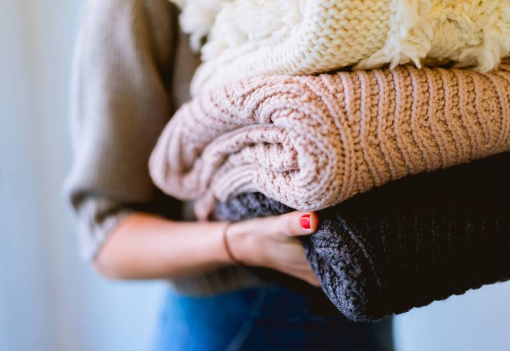 woman carrying second hand wool clothes