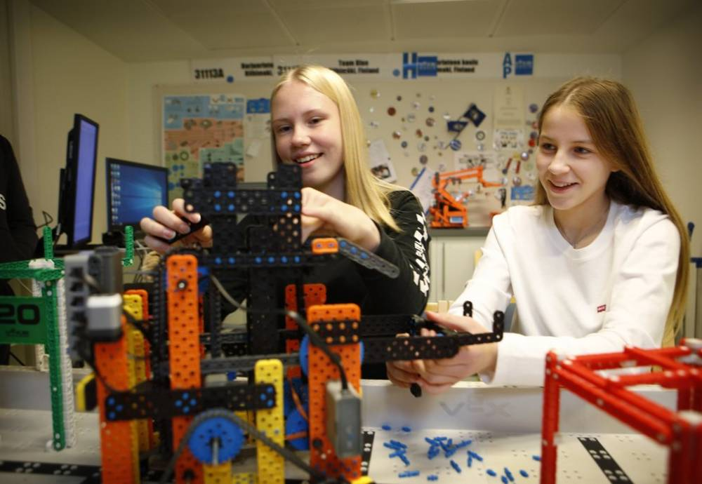 Two young students work on a robotics model