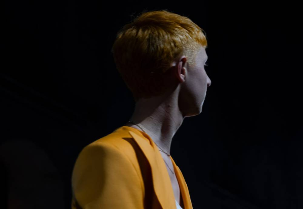 red-haired person in orange blazer looking away