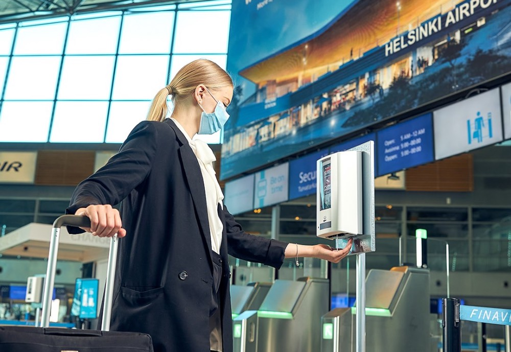 Woman applying hand disinfectant at Helsinki Airport