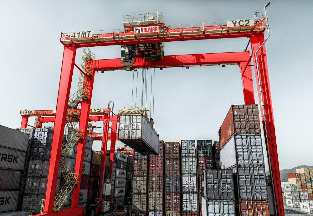 A Kalmar rubber-tyred gantry (RTG) crane lifting a container at a port