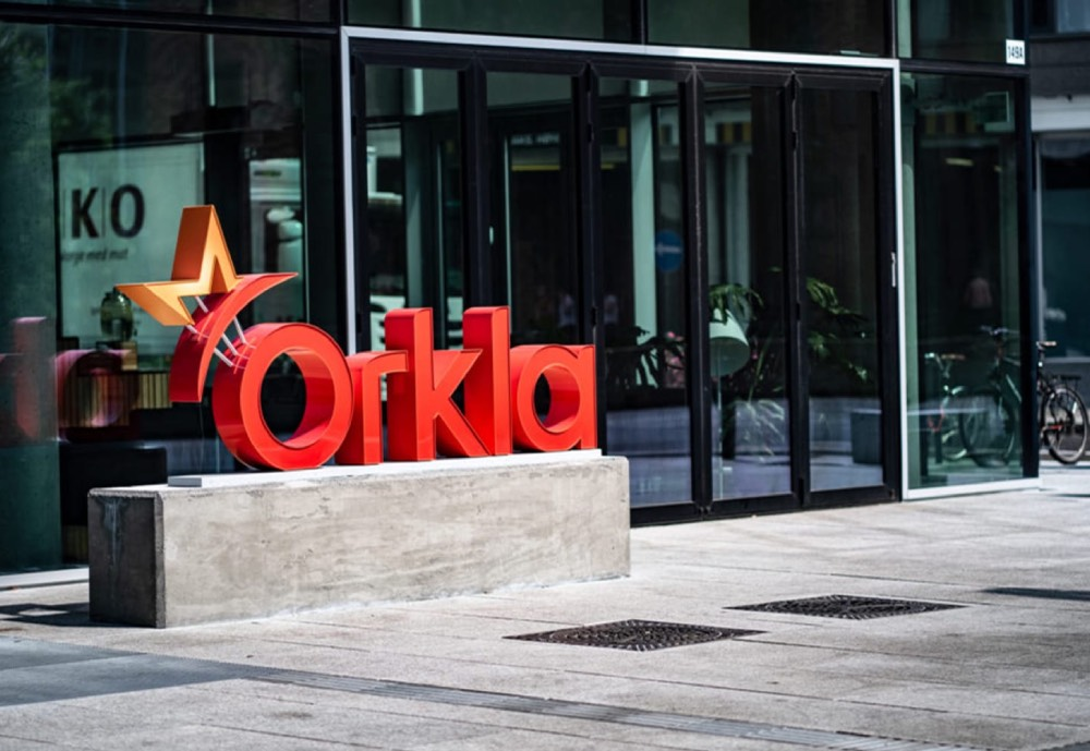 A red Orkla sign outside a building