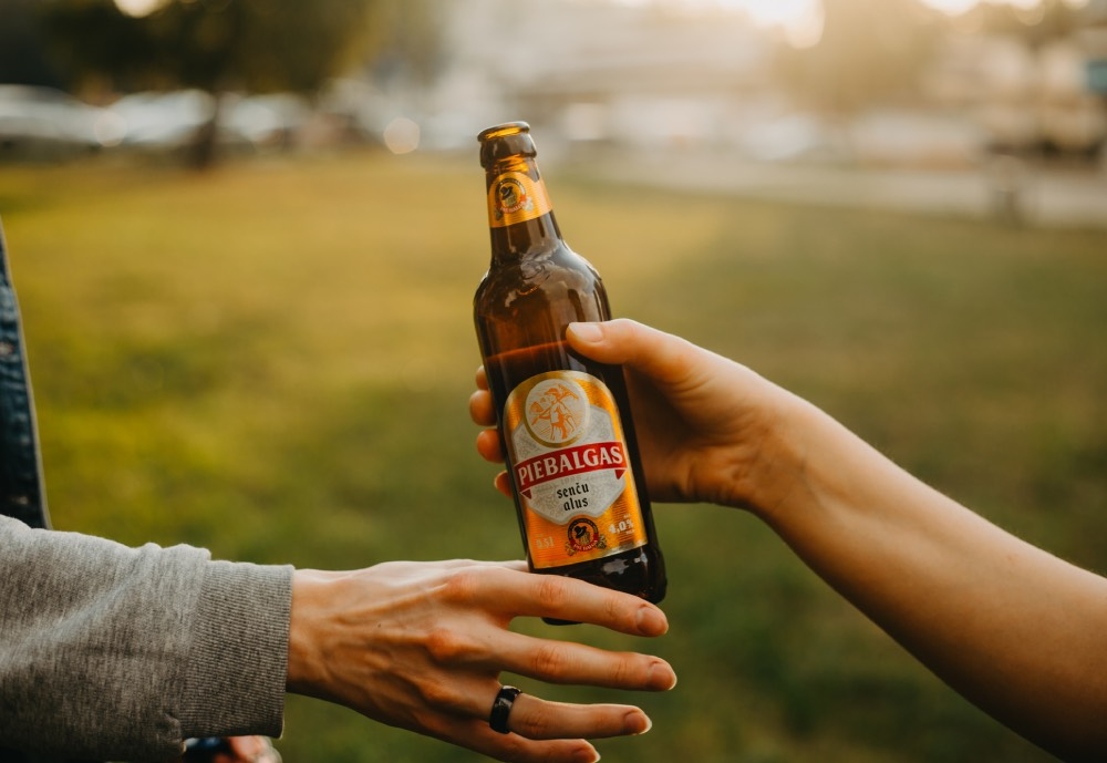 A beer being handed over in a park