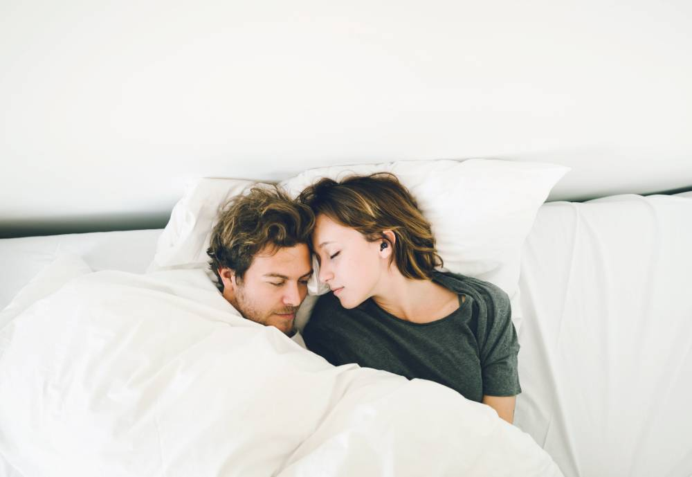 couple sleeping in white sheets