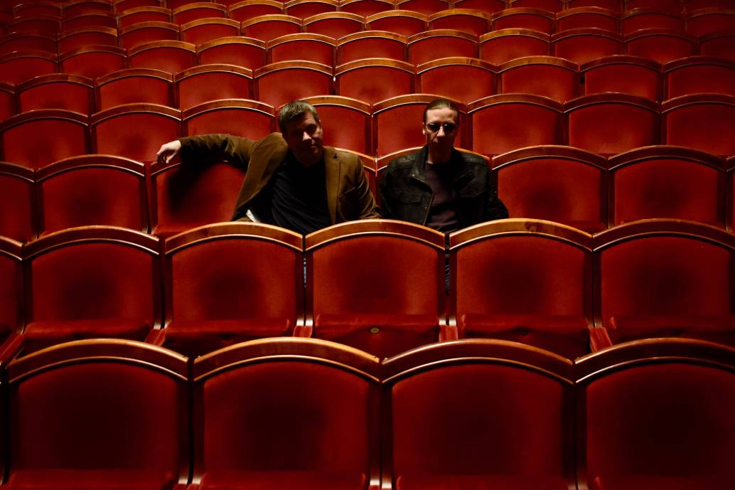 two men in an empty row of chairs