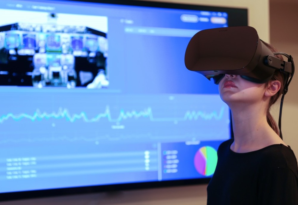 Woman wearing VR glasses next to a screen displaying analytical information