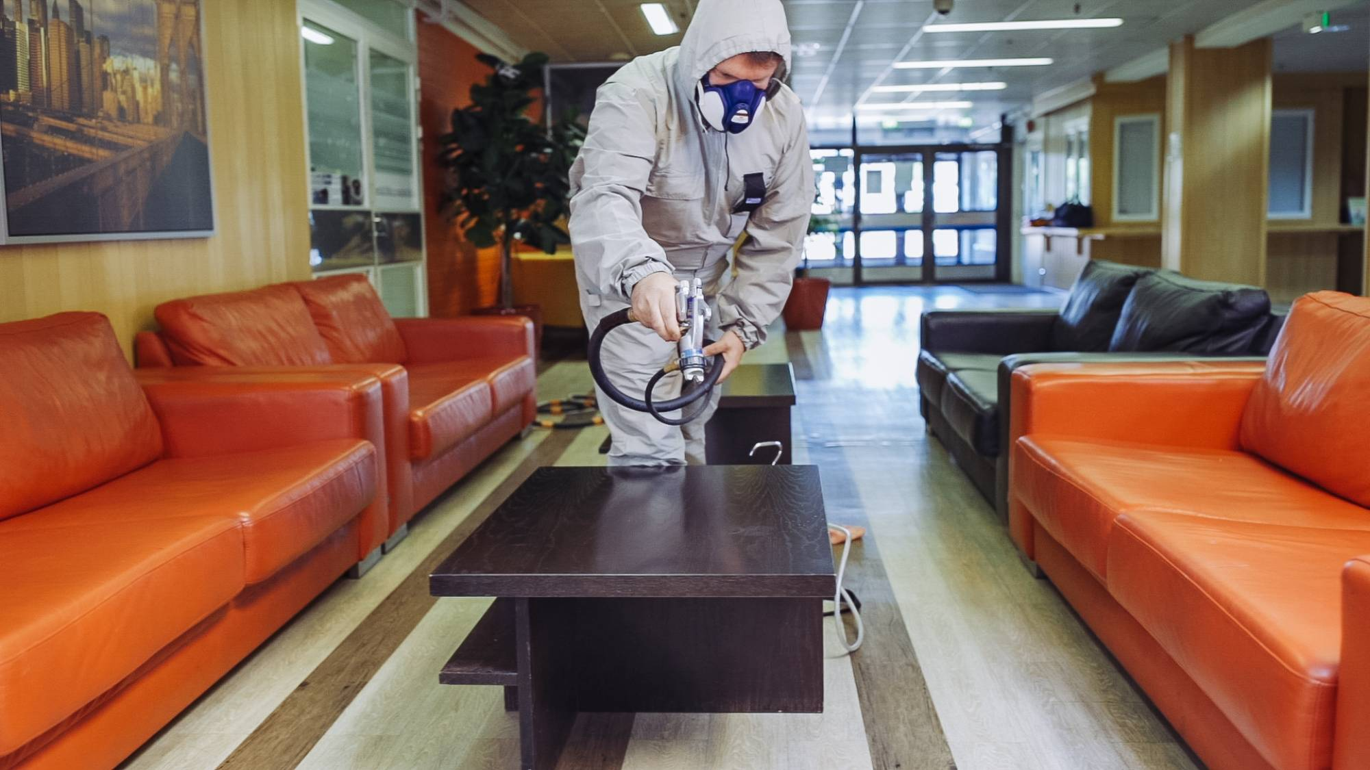 A man in a protective overall sprays substance on a table