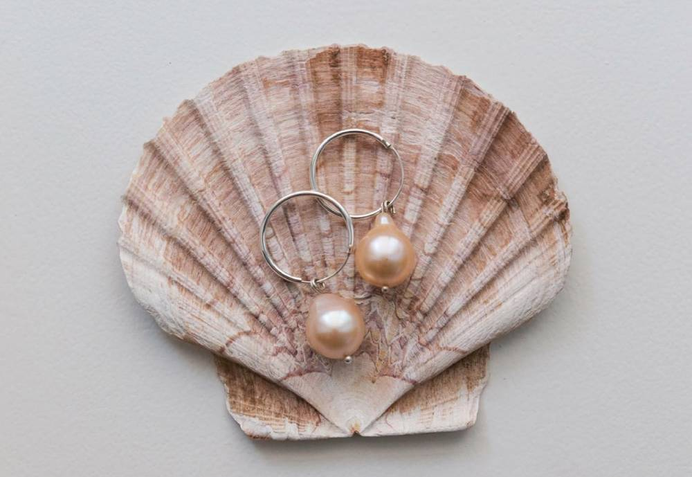 Pair of earrings on a clam shell