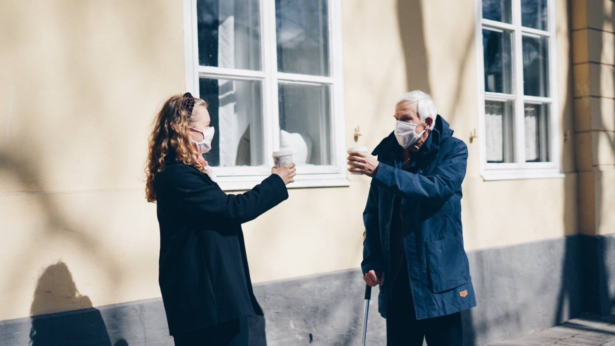 man and woman wearing masks drink coffee