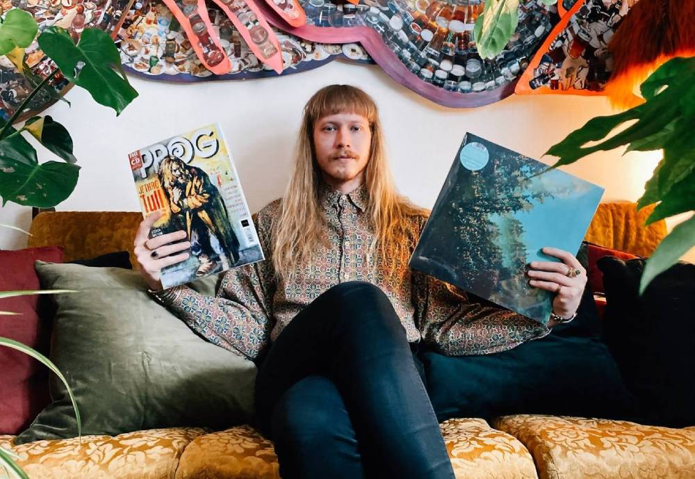 Polymoon band member sitting on couch with a record and magazine