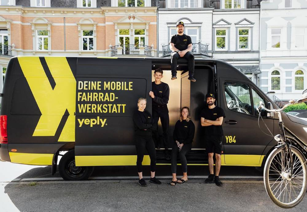 People posing with a Yeply van