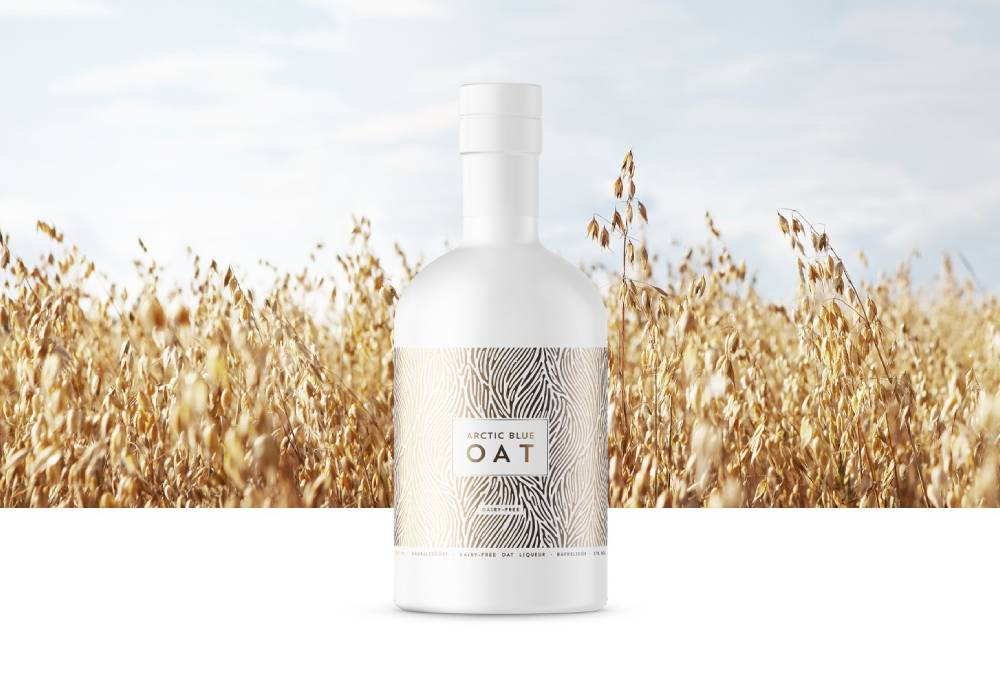 A white liqueur bottle with a golden label photographed against an oat field.
