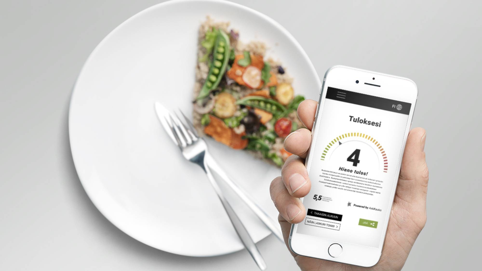 A hand holding a smartphone over a plate of leftover food.