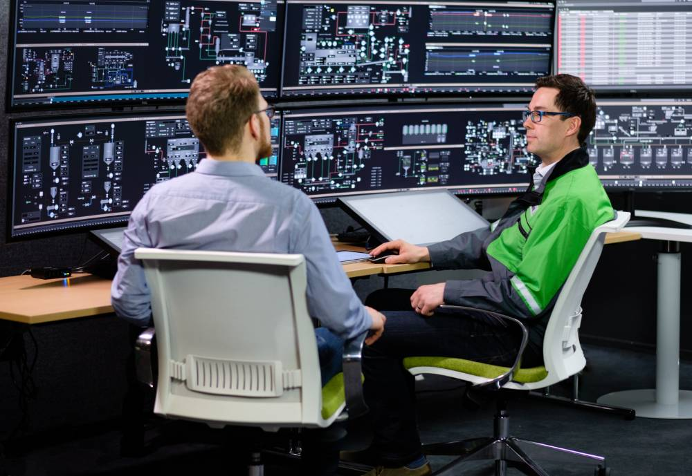 Two people talking at a desk in a monitoring room.