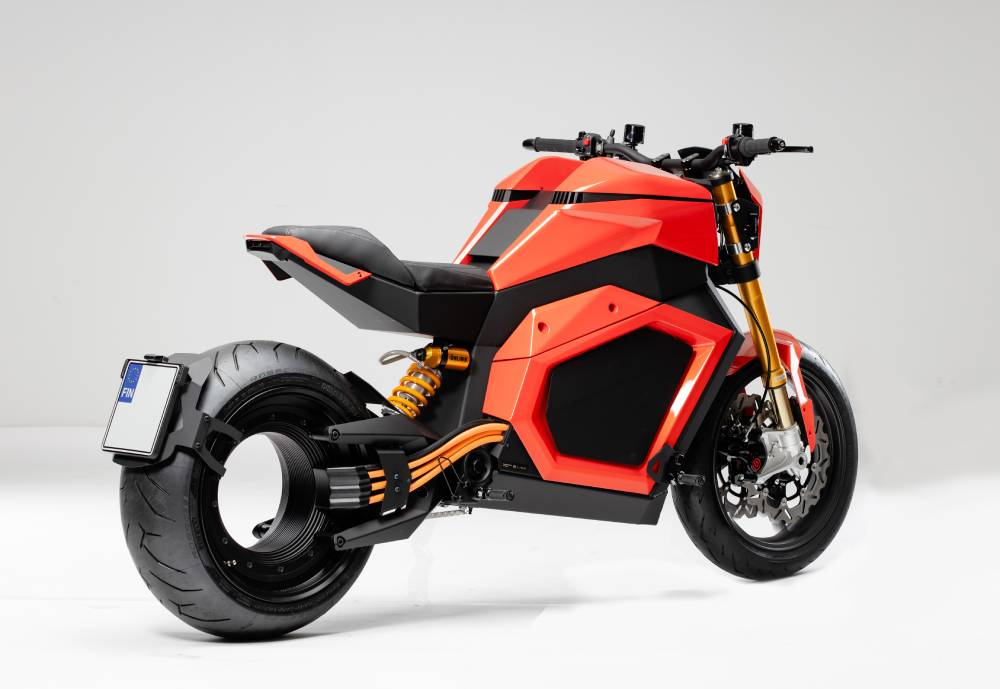 A black-and-orange motorcycle photographed in a grey studio.