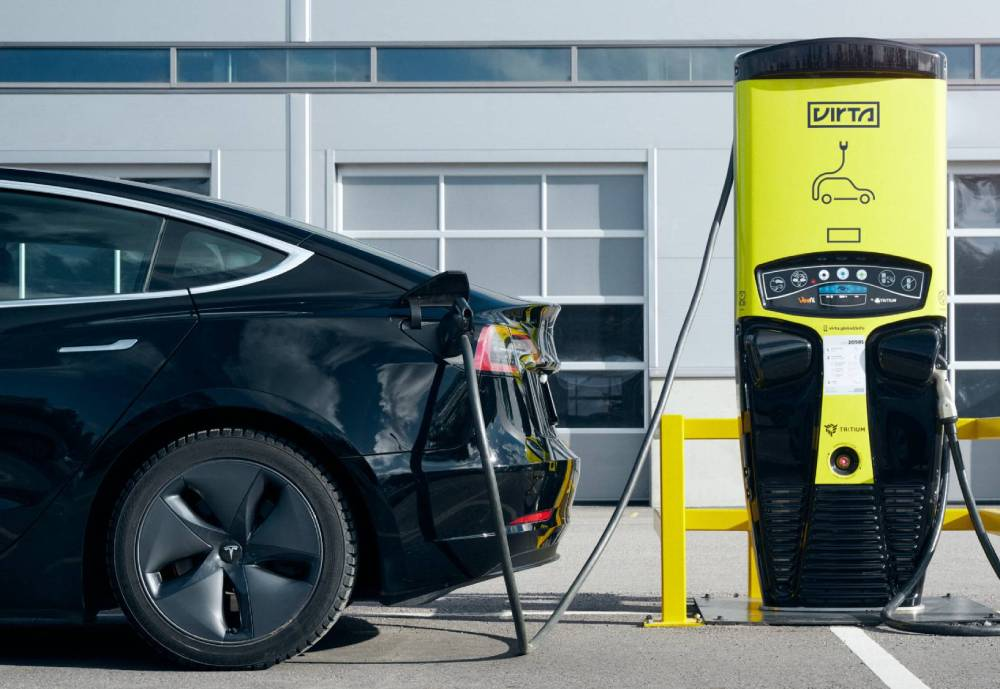 A black electric car plugged into a yellow power unit.