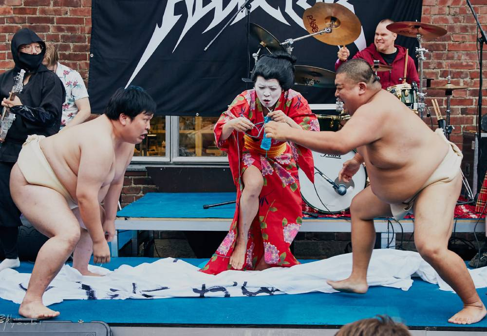 sumo wrestelers and a geisha participating in the Heavy Metal Knitting Championships