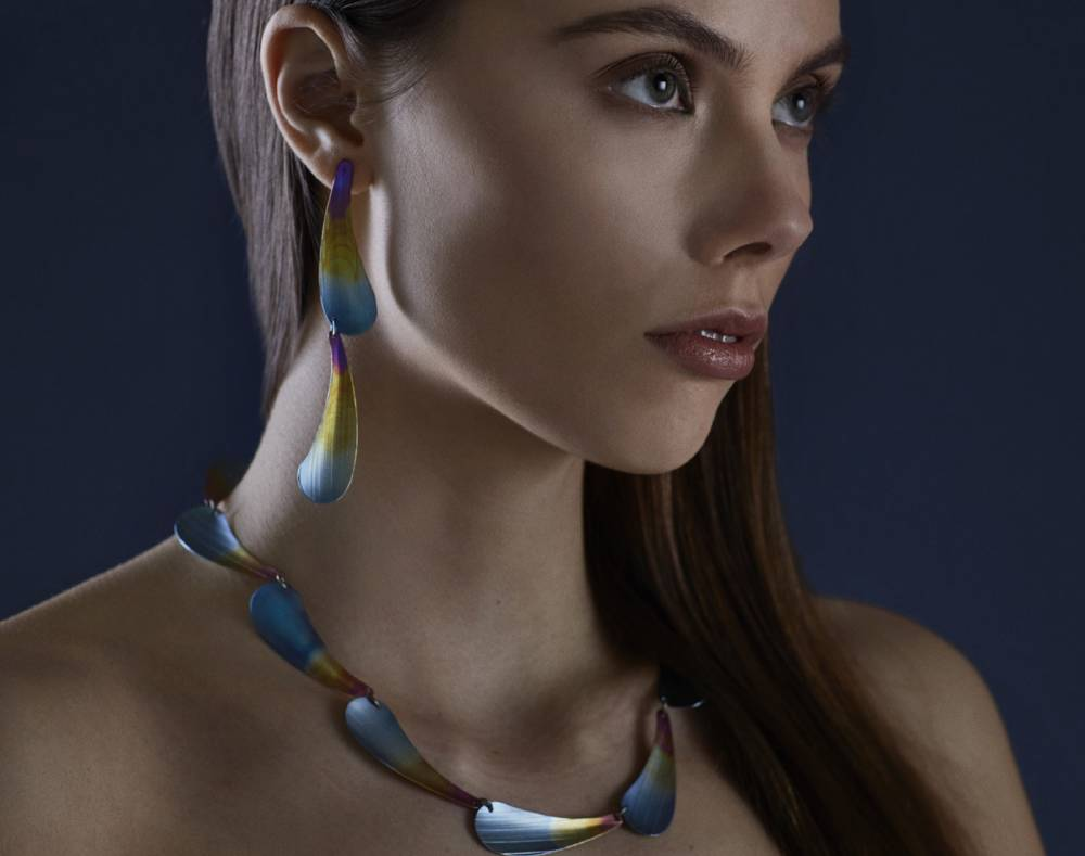 woman posing whilse wearing earrings and a necklace