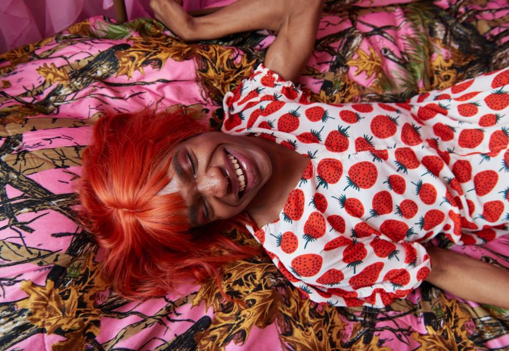 person laying on bed with a Marimekko dress