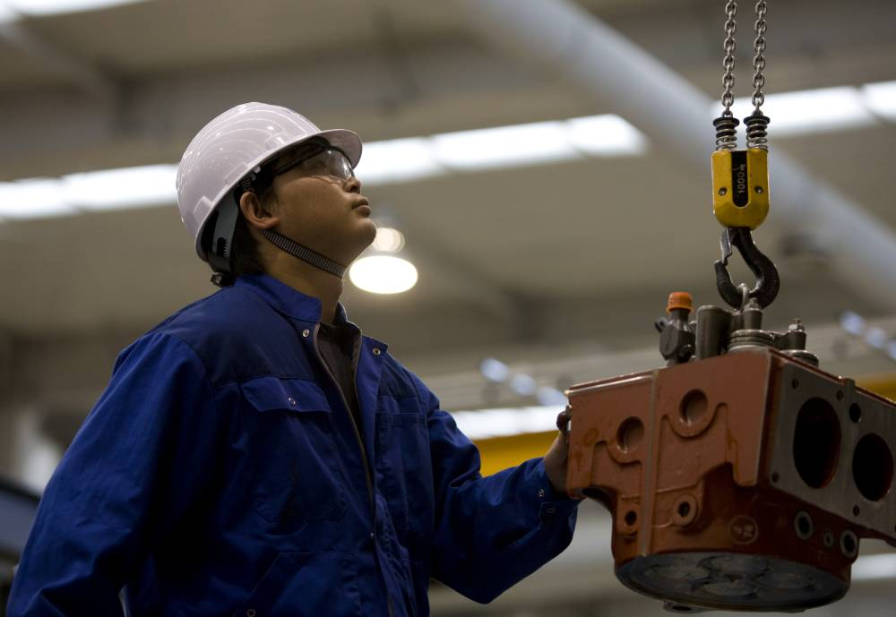 man looking up while working at a factory