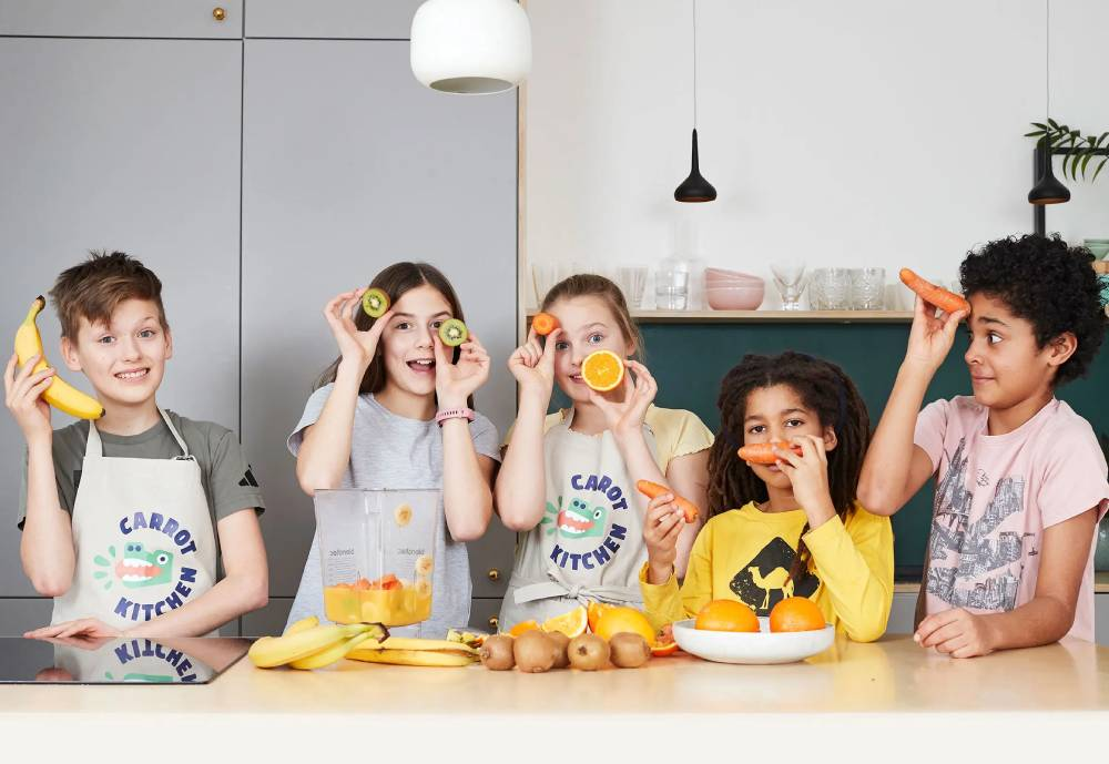 Five children posing for a photo in a kitchen while playing with fruits and vegetables.