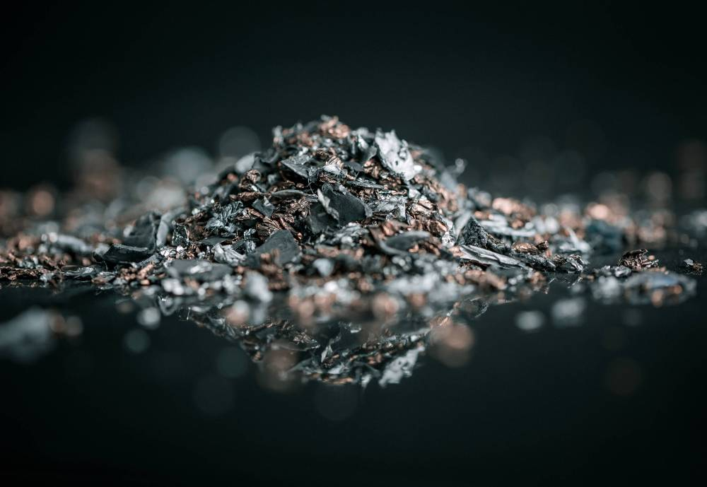 A pile of rare metals on a reflecting surface.
