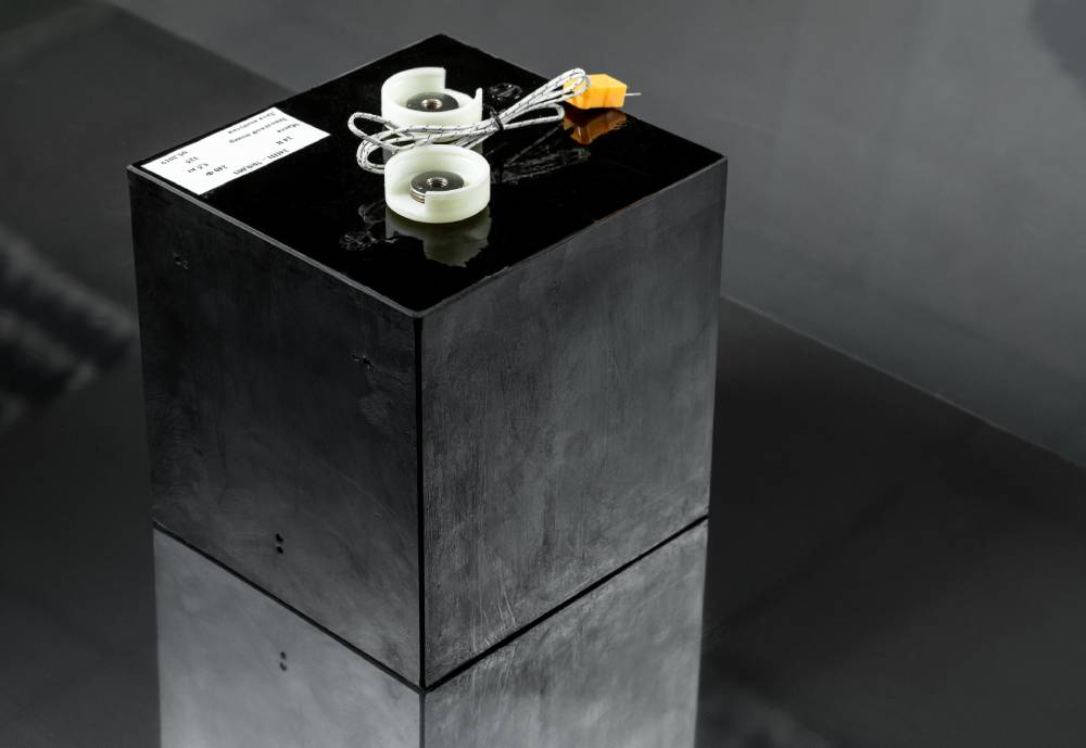 A black battery on a reflecting surface.