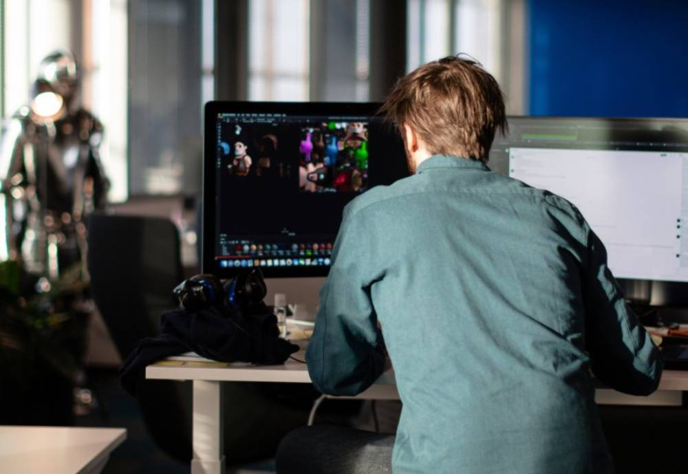 A programmer with his back to the camera sitting by a desk with two screens.