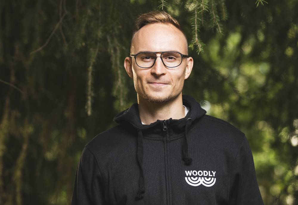 A man in a black hoodie posing for a photo in front of a spruce.