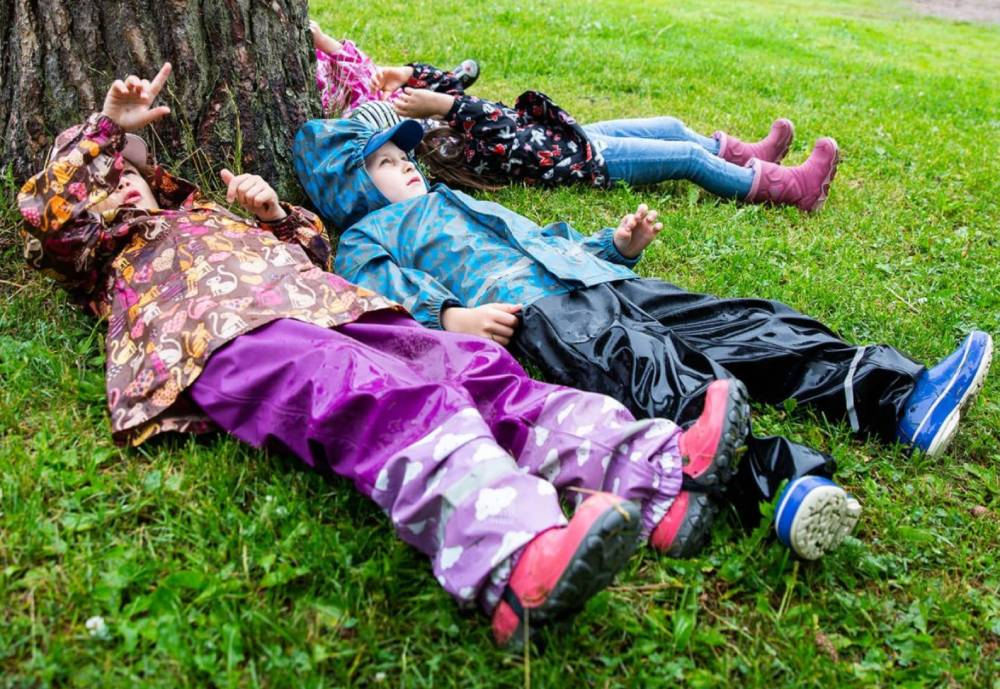 Kids lying on the grass under a tree