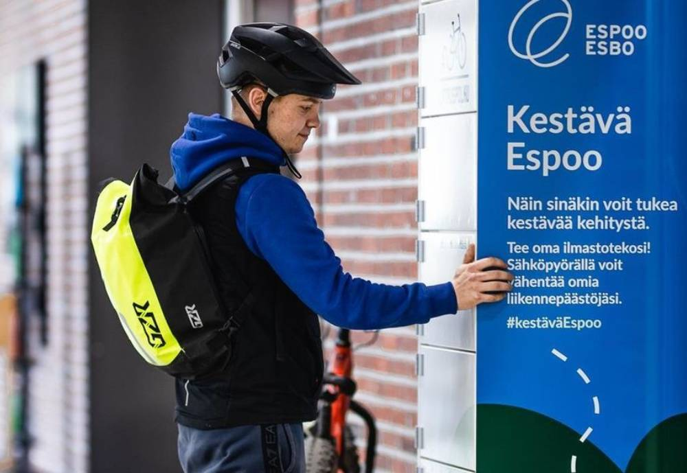 A man with a helmet and backpack standing next to a charging cabinet for e-bike batteries.