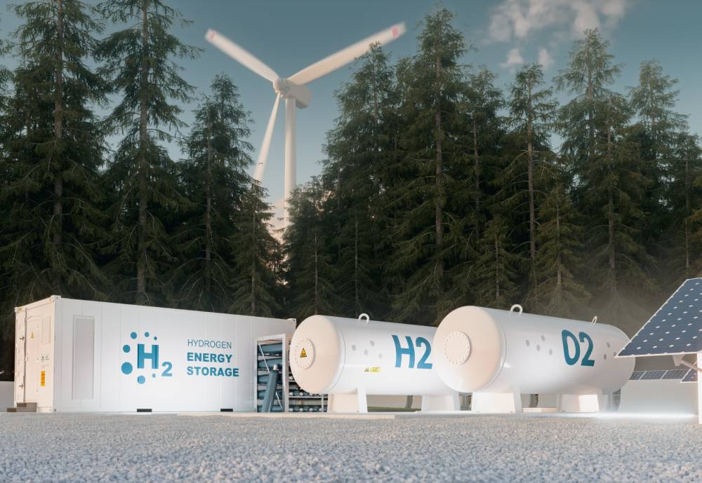 Hydrogen tanks in a man-made opening in a forest, next to solar panels and a wind turbine.