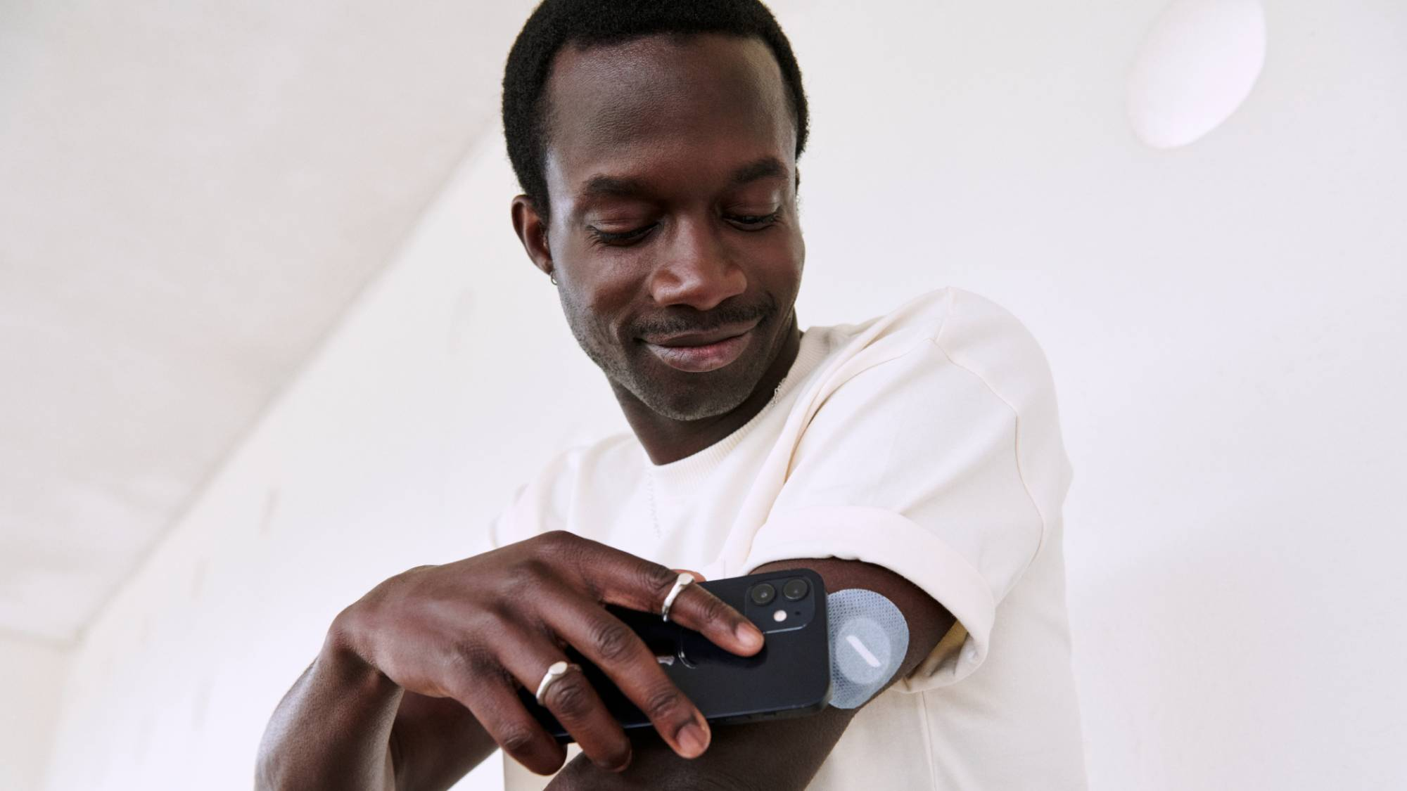 A man scanning a grey patch on his arm with a smartphone.