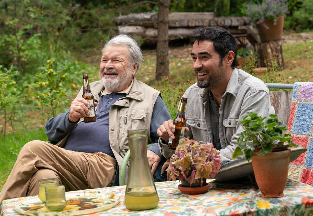 Two men sipping beer and laughing in a garden