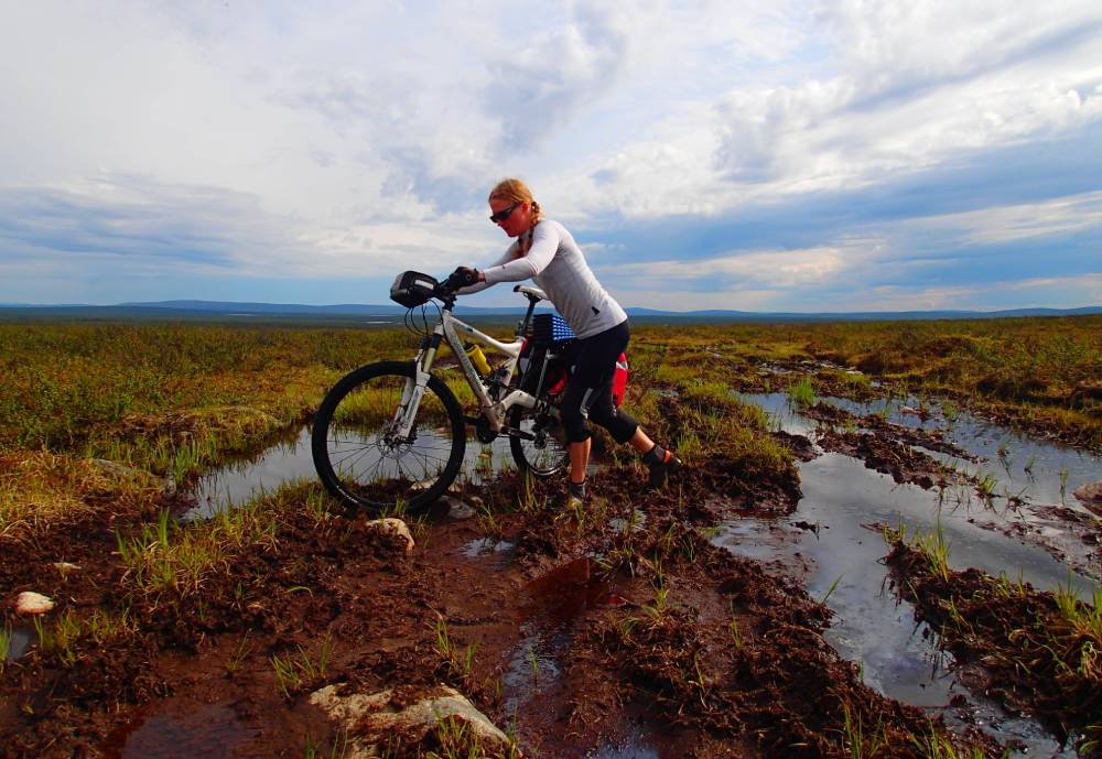 woman riding her bike on a swamp in Lapland
